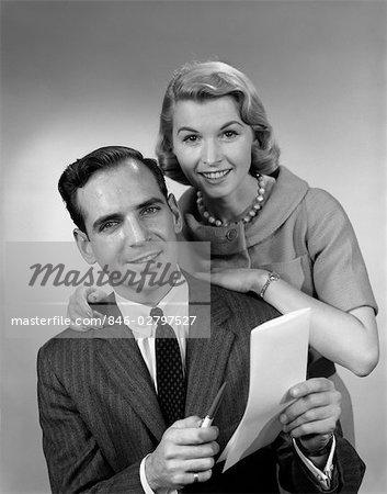 1950s COUPLE SMILING MAN HOLDING PEN PAPER