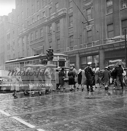 1950s PEDESTRIANS INTERSECTION CITY CROSS WALK UMBRELLAS RAIN WEATHER WET TROLLEY CAR PHILADELPHIA