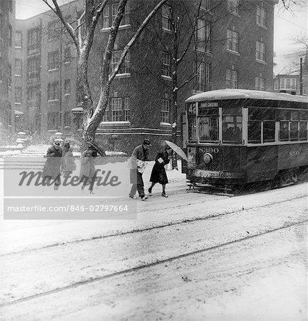 1940s CITY WINTER SCENE PEDESTRIANS CROSSING STREET SNOW TROLLEY CAR TRANSPORTATION