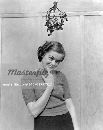 1930s 1940s GIRL STANDING UNDER MISTLETOE SMILING HAND NEAR MOUTH LOOKS SHY