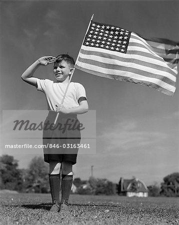 1940s BOY HOLDING AMERICAN FLAG SALUTING WEARING SHORT PANTS