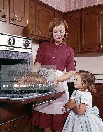 1960s COOKING TURKEY MOTHER DAUGHTER TURKEY THANKSGIVING
