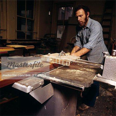 1970s MAN WORKING IN WOODSHOP WORKSHOP SAW WOODWORKING