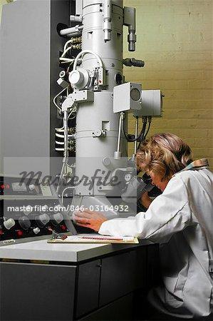 1970s LABORATORY WOMAN TECHNICIAN USING ELECTRON MICROSCOPE