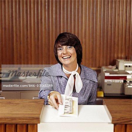 1970s SMILING WOMAN BANK TELLER HANDING CASH OVER COUNTER