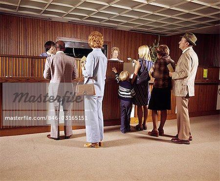 1970s LINE OF MEN WOMEN CHILDREN WAITING FOR BANK TELLER
