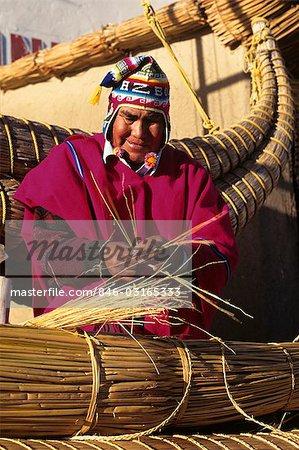 BOLIVIA LAKE TITICACA AYMARA INDIAN MAN BUILDING REED BOAT