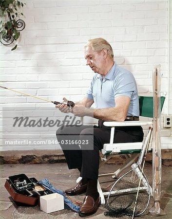 1960s SENIOR MAN SITTING DIRECTORS CHAIR HOLDING FISHING ANGLING ROD REEL