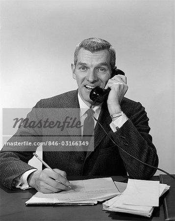 1960s 1950s BUSINESS MAN PHONE DESK PAPER WORK TALKING WRITING