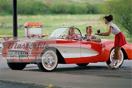 1990s COUPLE IN 1950s CORVETTE WAITRESS ON ROLLER SKATES AT CAR HOP GRANBY COLORADO USA