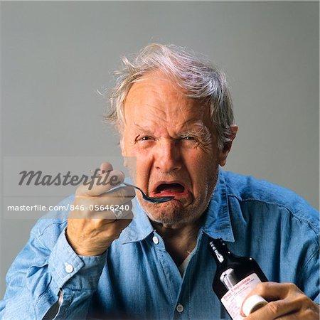 1970s SENIOR MAN TAKING SPOONFUL OF MEDICINE WITH BAD TASTE