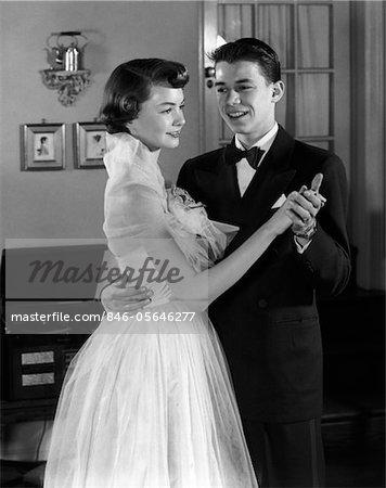 1950s SMILING TEENAGE COUPLE IN FORMAL EVENING WEAR DANCING INDOORS