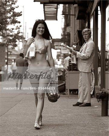 1970s MAN OGLING SEXY SMILING YOUNG WOMAN WALKING DOWN CITY STREET WEARING ONLY A BIKINI BATHING SUIT