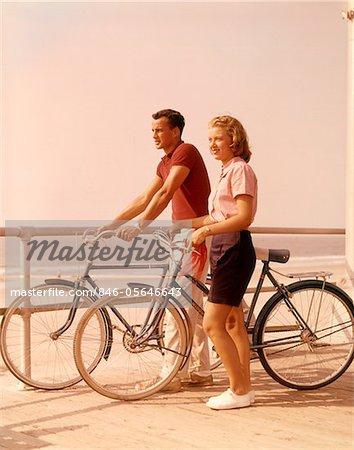 1950s - 1960s TEEN COUPLE STANDING BY BIKES ON  BEACH BOARDWALK