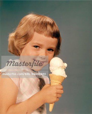 1950s - 1960s SMILING  GIRL EATING ICE CREAM CONE DOUBLE SCOOP VANILLA