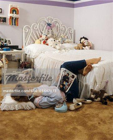 1980s teenage girl lying on bedroom floor reading magazine talking 1980s teenage girl lying on bedroom floor reading magazine talking on telephone stock photo sisterspd
