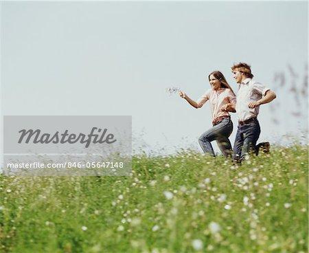 1970s  YOUNG TEEN COUPLE BOY GIRL RUNNING FIELD  WILDFLOWERS