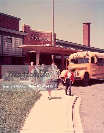 1950s GROUP ELEMENTARY SCHOOL KIDS BOYS GIRLS WALKING AWAY BUS BUILDING SIDEWALK EDUCATION
