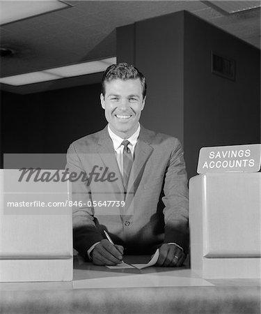1960s SMILING MAN BANK TELLER SAVINGS ACCOUNTS SIGN ON COUNTER