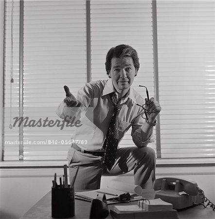 1970s BUSINESSMAN STANDING BEHIND DESK ARM RAISED IN PLEADING GESTURE