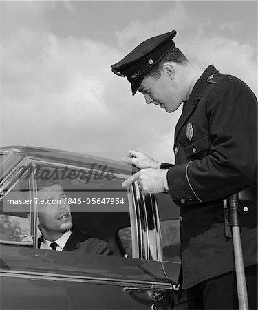 1960s POLICE OFFICER WARNING MOTORIST POINTING FINGER AT DRIVER