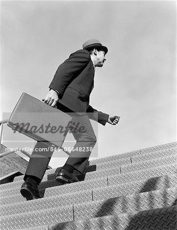 1960s SALESMAN BUSINESSMAN BRIEFCASE IN HAND CLIMBING STEEP HARD STEEL TREAD STAIRS SYMBOLIC OUTDOOR