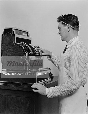 1920s - 1930s MAN WEARING APRON RINGING UP SALE ON CASH REGISTER