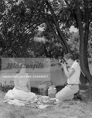 1950s TEENAGE COUPLE PICNIC BOY TAKING PHOTOGRAPH OF GIRL OUTDOORS