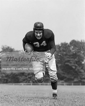 1940s FOOTBALL PLAYER HOLDING FOOTBALL RUNNING FORWARD LOOKING AT CAMERA