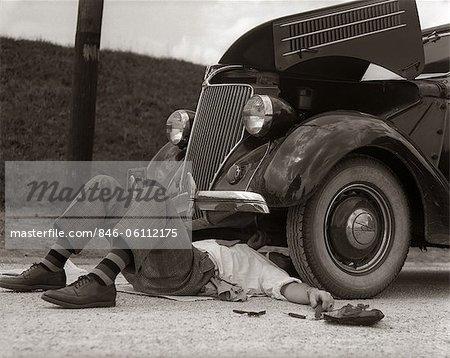 1930s MAN ON BACK WEARING STRIPED SOCKS FIXING CAR