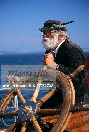 MATURE BEARDED MAN AT WHEEL OF SHIP