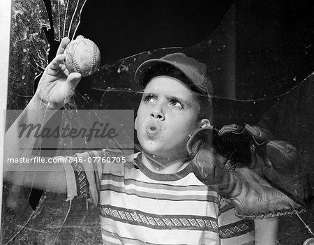 1950s BOY IN TEE-SHIRT & CAP REMOVING BASEBALL FROM BROKEN WINDOW