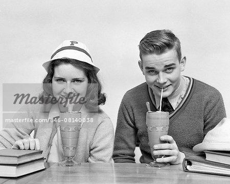 1940s TEENAGE BOY AND GIRL DRINKING MILKSHAKES TOGETHER LOOKING AT CAMERA