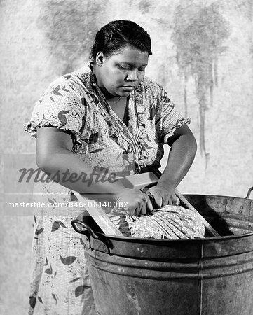 1930s AFRICAN-AMERICAN WOMAN WASHING SCRUBBING CLOTHES ON WASHBOARD IN A GALVANIZED ZINC WASHTUB