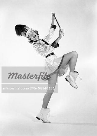 1960s WOMAN MAJORETTE BAND UNIFORM SHORT SKIRT BOOTS TASSELS MARCHING ONE LEG UP HOLDING BATON SMILING