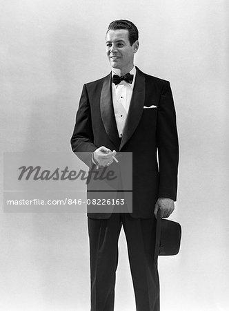 1950s PORTRAIT SMILING MAN WEARING TUXEDO HOLDING CIGARETTE AND FEDORA HAT