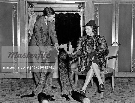 1930s WOMAN IN FUR SALON WEARING FUR COAT SITTING DOWN WHILE SALESMAN SHOWS HER FOX FUR STOLES