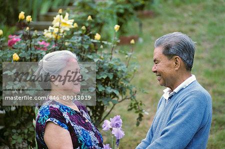 SENIOR ELDERLY ASIAN COUPLE LAUGHING IN GARDEN