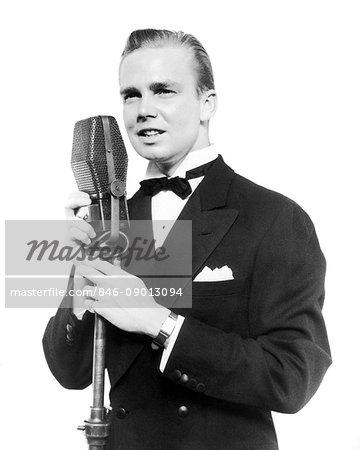 1920s 1930s SMILING MAN RADIO SINGER ENTERTAINER CROONER IN TUXEDO SINGING INTO MICROPHONE