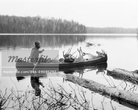 1920s MAN HUNTING GUIDE PADDLING CANOE IN LAKE CARRYING MOOSE AND DEER CARCASSES