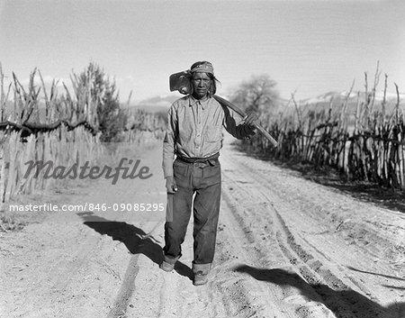 1930s NATIVE AMERICAN INDIAN MAN FARMER WALKING ROAD CARRYING FARM TOOL HOE SAN ILDEFONSO PUEBLO NEW MEXICO USA