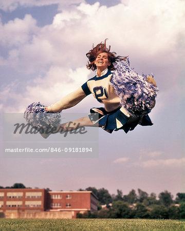 1960s 1960s GIRL CHEERLEADER IN MID AIR SPLIT JUMP SMILING BLUE & WHITE UNIFORM SKIRT POMPOMS JUMPING LEVITATE