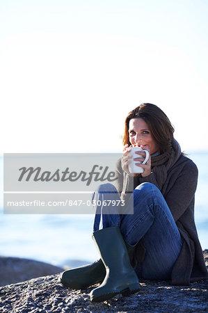 Beautiful lady drinking tea on the beach