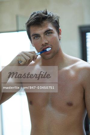 Handsome man brushing teeth
