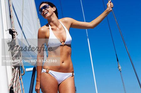 Girl in white bikini standing on sailing boat
