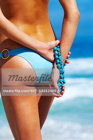 Beautiful woman with bare back and bikini bottoms on sandy beach