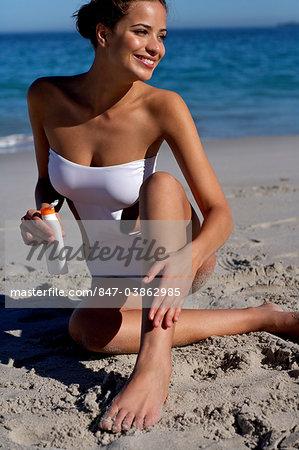 Beautiful brunette applying suncream on the beach