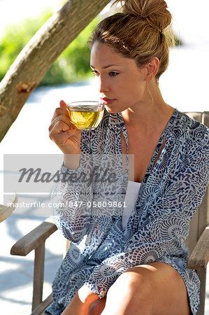 Beautiful girl sitting outside drinking herbal tea