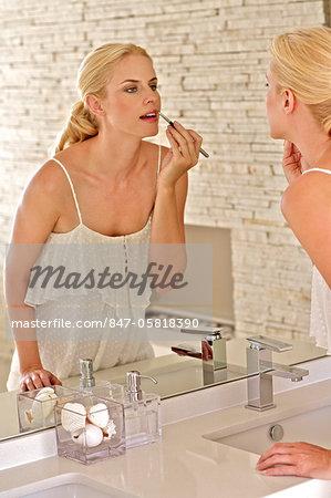 Beautiful blonde woman applying lipgloss