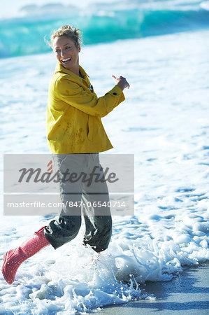 Beautiful mature woman standing in jacket in sea